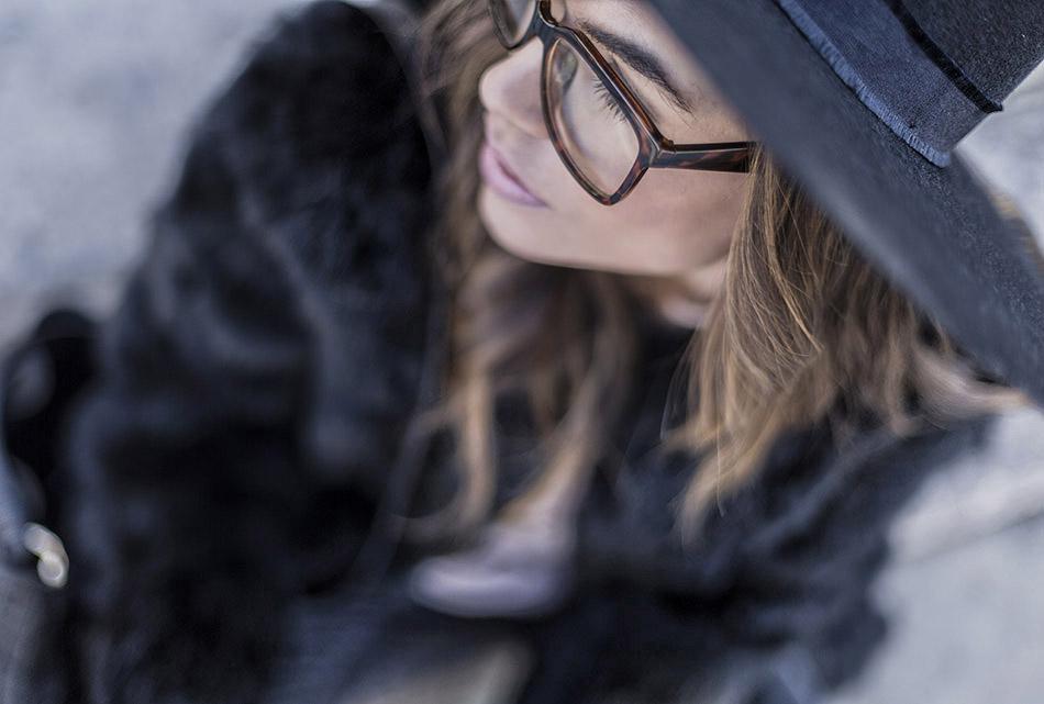 look de street style con abrigo de pelo negro, camiseta bordada de tul  de color rosa de Zara, jeans pitillo negro, botines y sombrero de ala ancha rigida