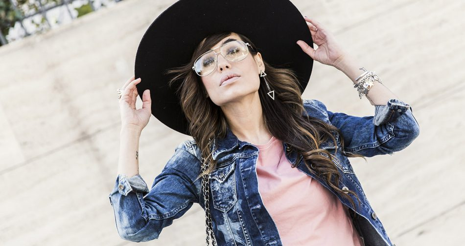 look de street style con sombrero negro de ala ancha rígida, cazadora denim de pepe jeans, camiseta rosa , pantalones negros con volante en el bajo y gafas de ver de Zara
