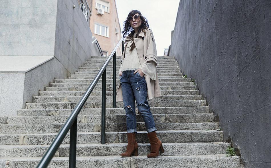 look de street style con gabardina con  parches, blusa de encaje, pantalones boyfriend rotos y botines de ante color caramelo