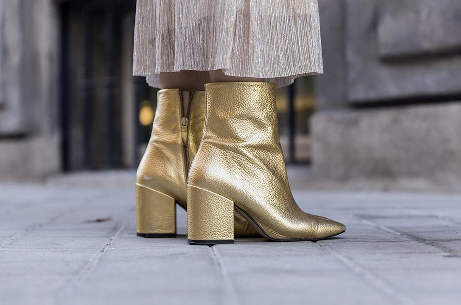 look de street style con blazer de terciopelo verde, camiseta blanca, falda midi plisada de color dorado y botines dorados