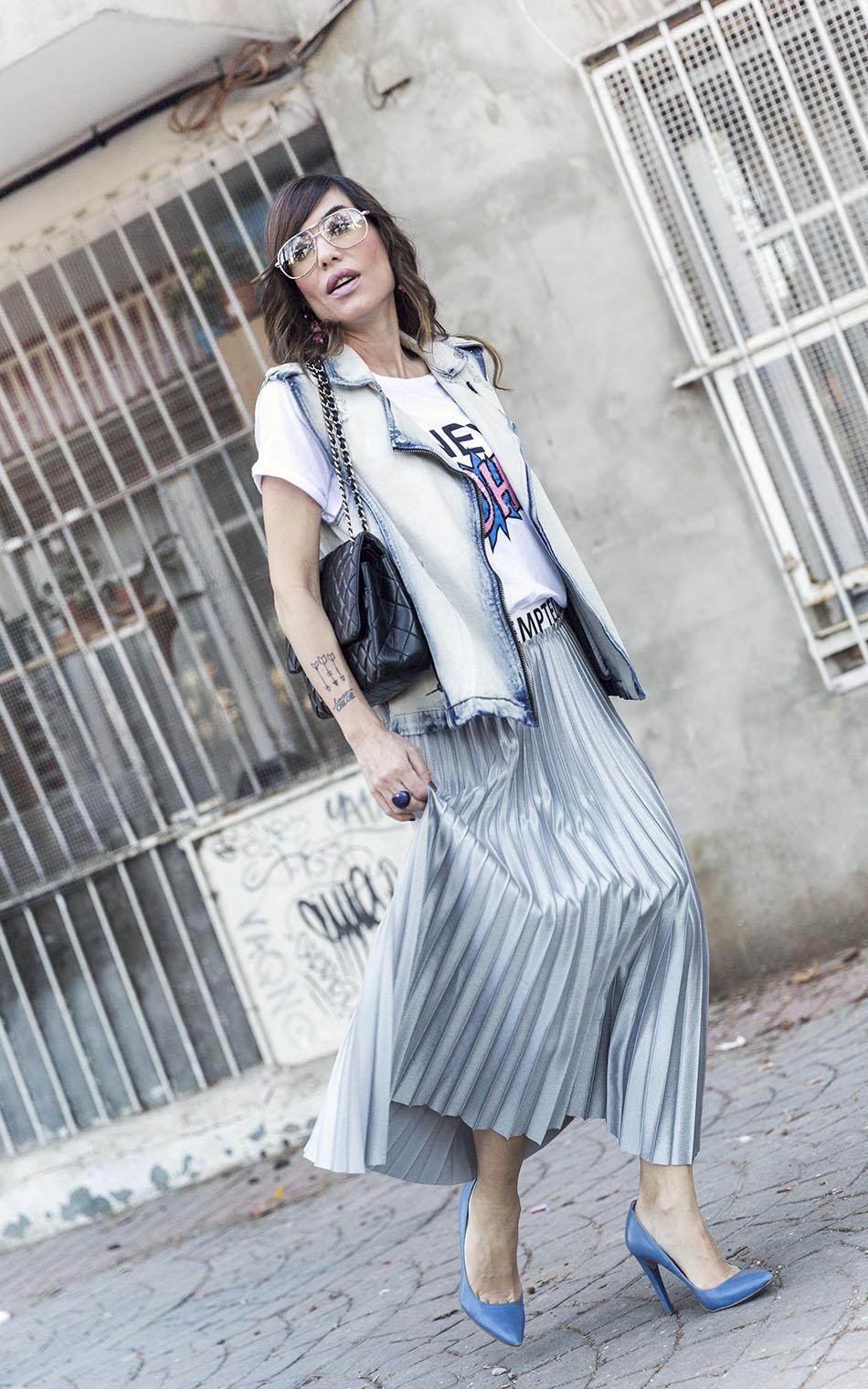 look de street style con chaleco vaquero, camiseta de Mango con texto New York, falda plisada de color plata, zapatos de salon azules y bolso plateado