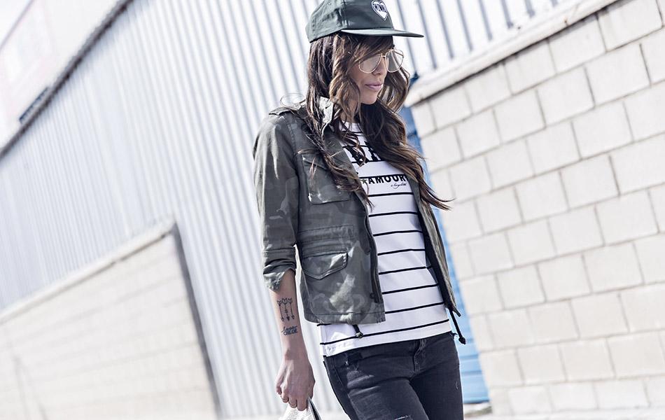 look de street style con chaqueta de estampado militar, camiseta de estampado navy, pantalones pitillos negros desgastados y botines negros