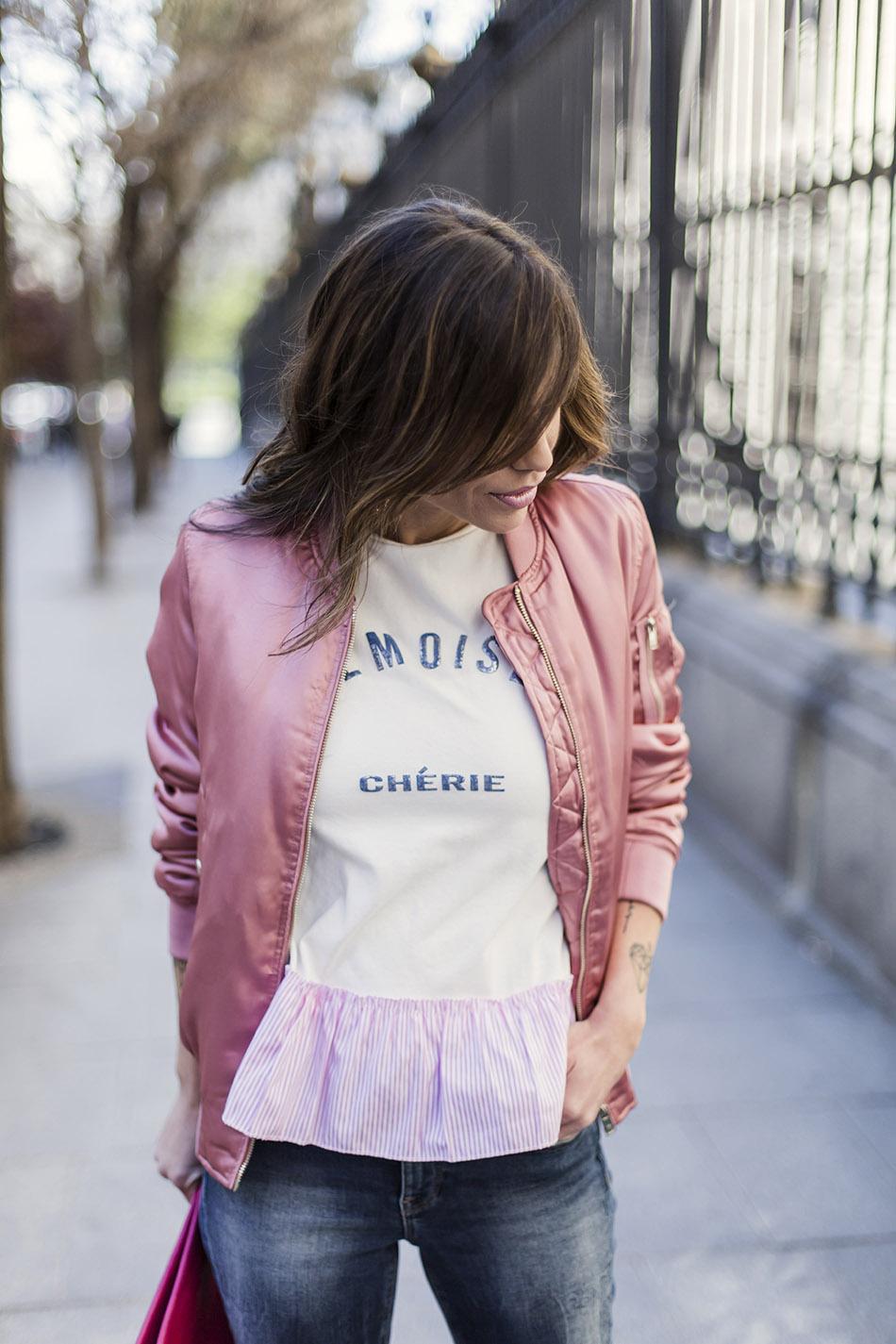 look de street style con camiseta blanca con mensaje y detalle de volante rosa en el bajo, pantalones jeans pitillos, botines plateados y bomber rosa