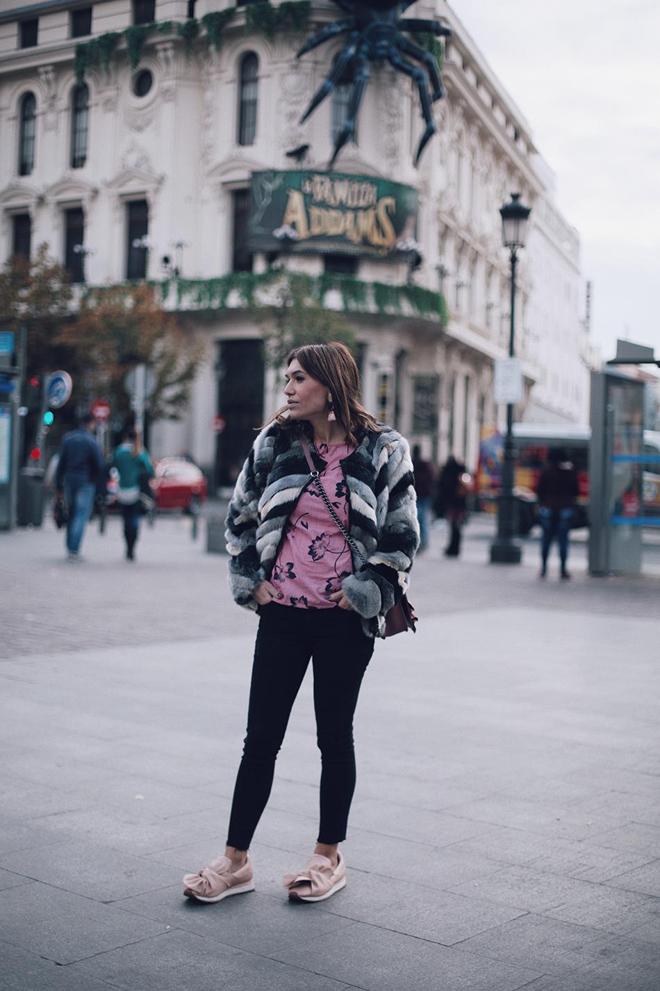 street style de Bárbara Crespo con abrigo de pelo gris, blusa rosa de flores y rayas de Kiabi , jeans skinny y sneakers de color rosa. Foto en la plaza de Jacinto Benavente
