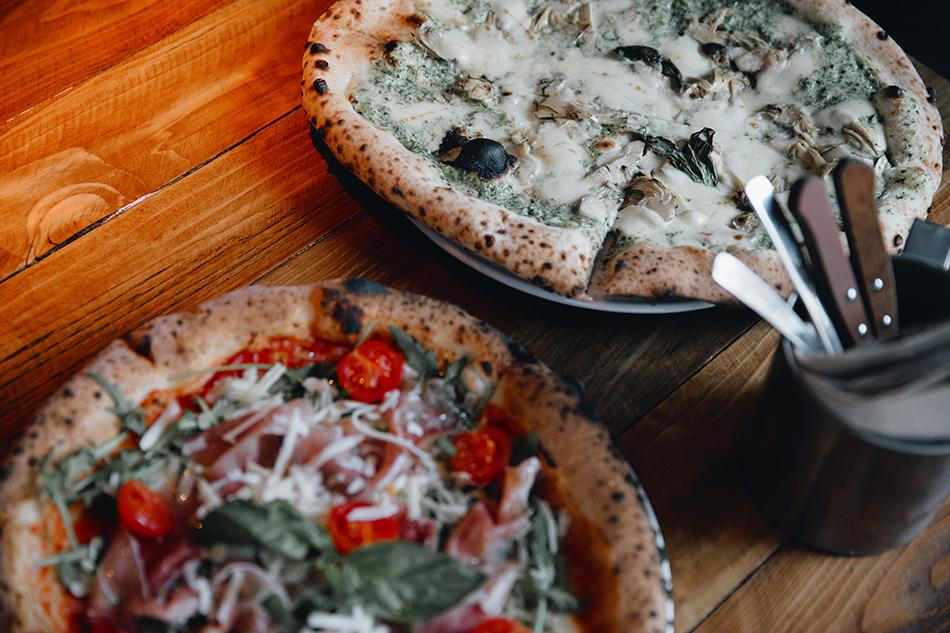 pizza de crema y alcachofas y pizza de tomates cherry, jamón de parma y queso parmesano