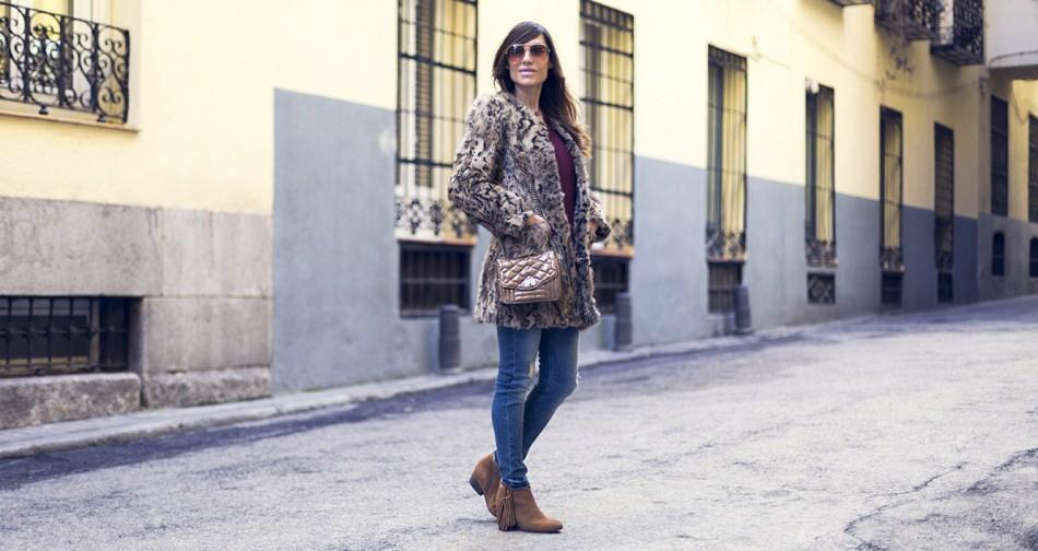 streetstyle con botines de flecos, jeans pitillos desgastados, abrigo de animal print y bolso pequeño acolchado en color dorado