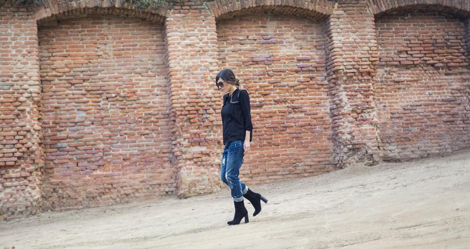 look de street style con blusa de color negro y ribete étnico , pantalones vaqueros estilo boyfiriend, botines de ante en color negro y gafas de sol