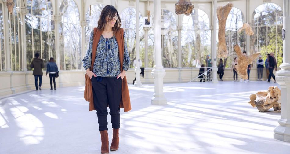 look de street style con chaleco de lana en color caramelo, blusa con print de paisley, pantalones de vestir azules y botines de ante en color caramelo