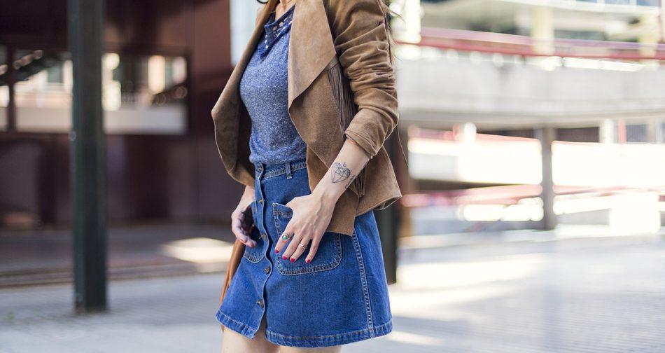 look de street style con chaqueta de ante y flecos de el corte inglés, camiseta con ribete étnico de en azul lavado , falda abotonada en el delantero en denim y botines de ante
