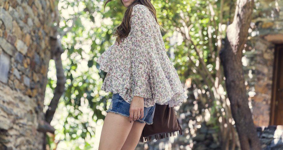 blusa con estampado de flores y escote en pico de Amitie de El Corte Inglés, combinada con short denim de Mango, bolso de cuero marrón tipo saco para llevar al hombro con detalle de flecos, gafas de sol aviator de Rayban y botines de ante de hakei