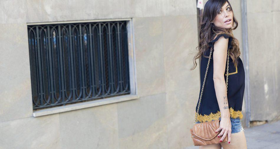 look de street style con top negro y ribete dorado de estilo romántico y shorts vaqueros