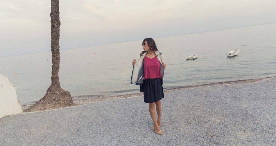 look de street style con chaleco denim, top de tirantes en color frambuesa, falda midi metalizada plisada y sandalias destalonadas en ante