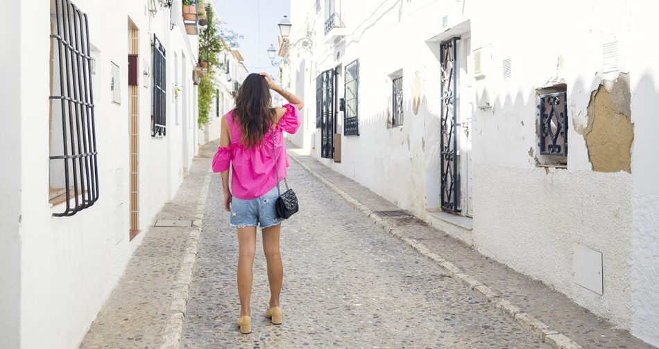 look de street style con top de color fucsia y estilo cut off the shoulders, shorts denim, zapatos bicolor estilo chanel de zara y bolso acolchado de hakei