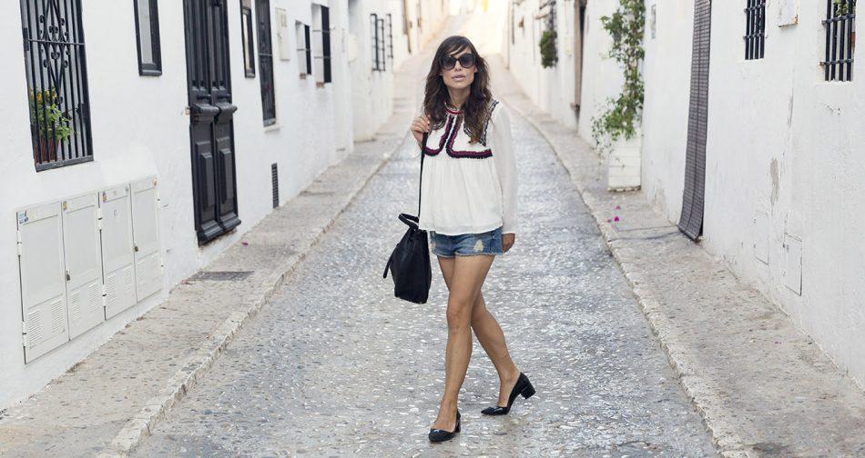 look de street style con blusa de color blanco y detalle de ribetes en la zona del pecho, shorts denim, zapatos de tacón midi ancho y bolso estilo saco de zara