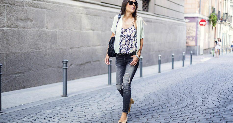 look de street style con cardigan en color verde manzana claro, top de tirantes de estampado floral, pantalones vaqueros desgastados en color gris y zapatos estilo Chanel bicolor con tacón cuadrado y puntera negra