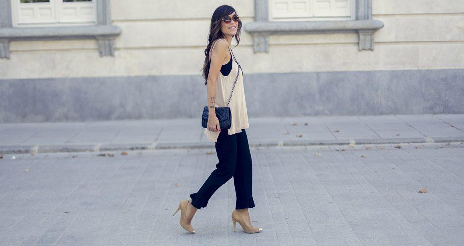 look de street style con top oversize de tirantes de punto en color beige de sheen, pantalones de vestir de zara en color negro con volante en el bajo