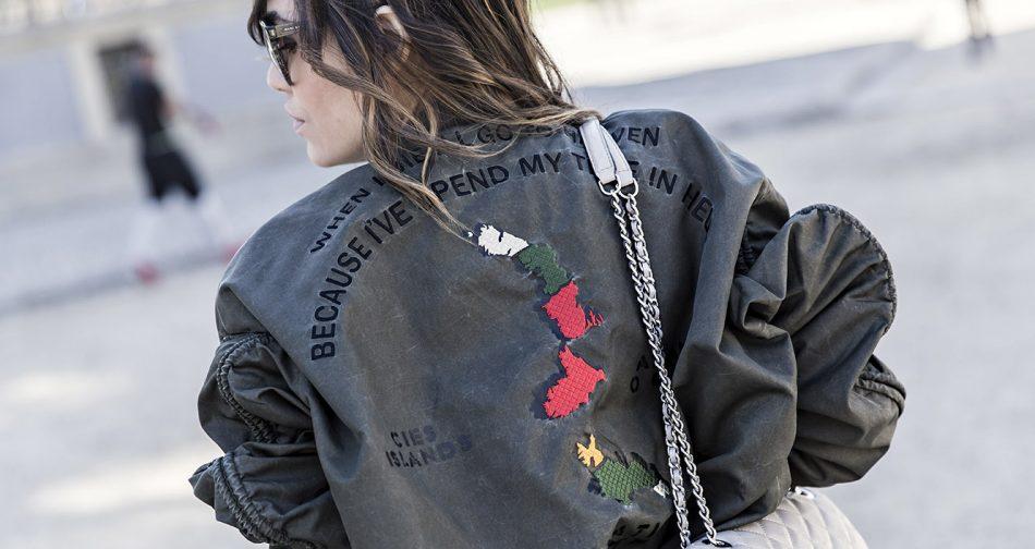 look de street style con chaqueta bomber verde khaki de Zara, Jeans desgastados, botas de estilo cowboy y bolso Michael Kors